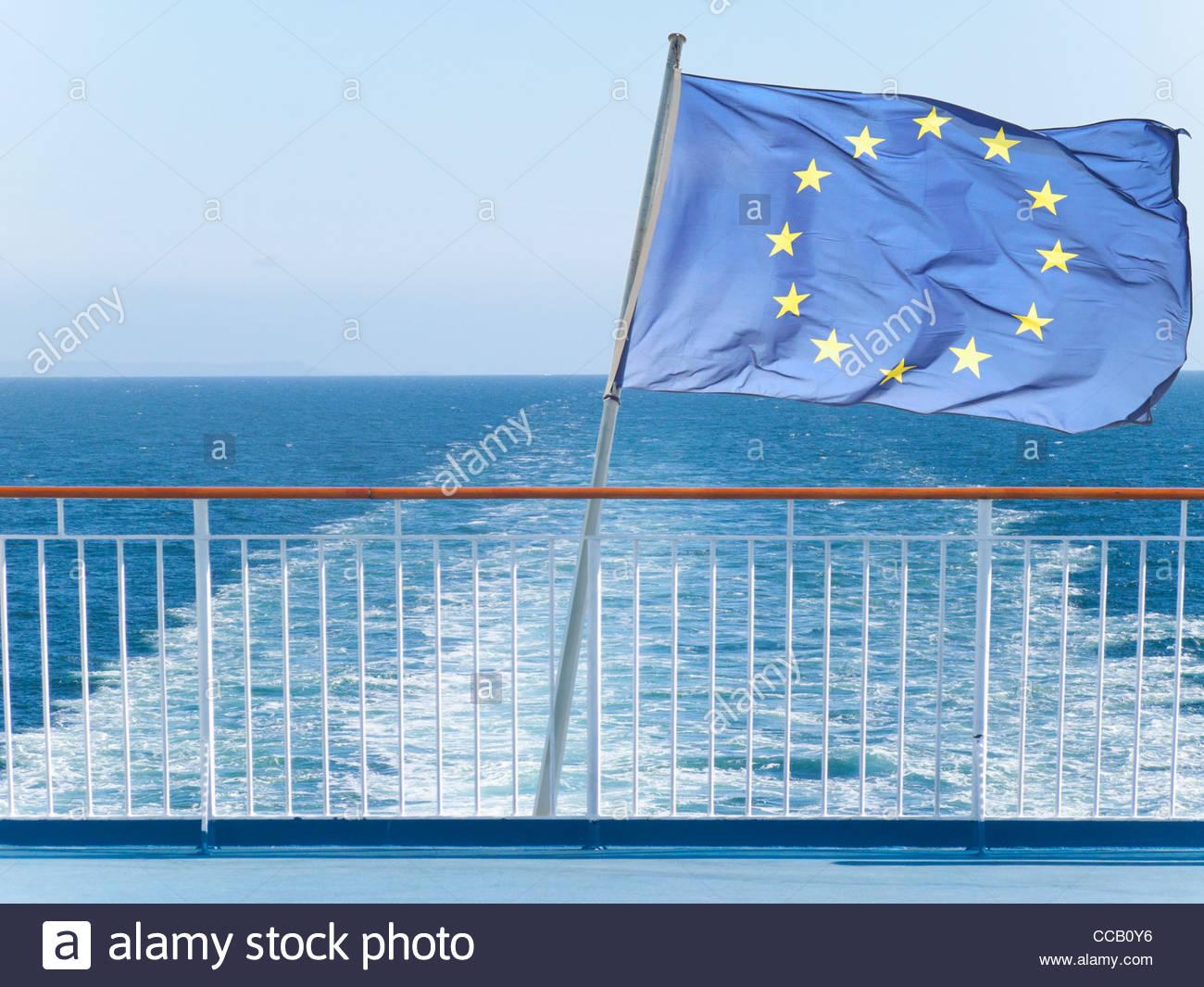 EU-Flagge auf der Reling des Schiffes mit Meerwasser im Hintergrund Stockbild