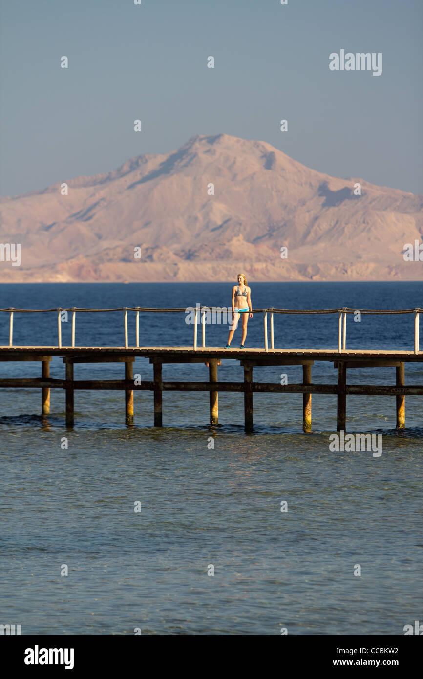 Mädchen im Badeanzug stehen auf dem Pier am Ufer des Roten Meeres. Tiran Insel im Hintergrund. Stockbild