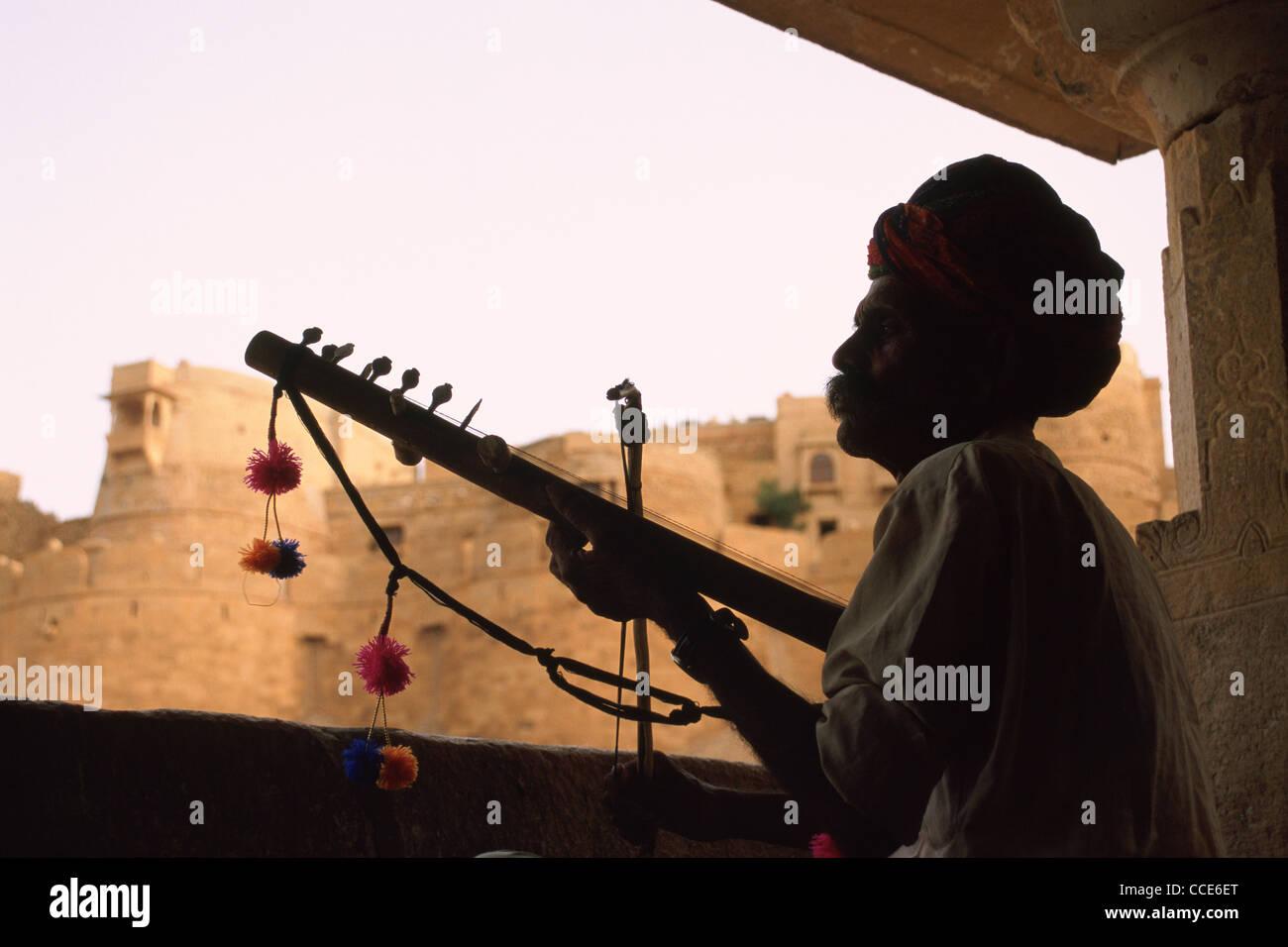 """Minnesänger (""""Bhopa"""" in Hindi) Musizieren vor ein historisches Denkmal (das Jaisalmer Fort) (Indien) Stockbild"""