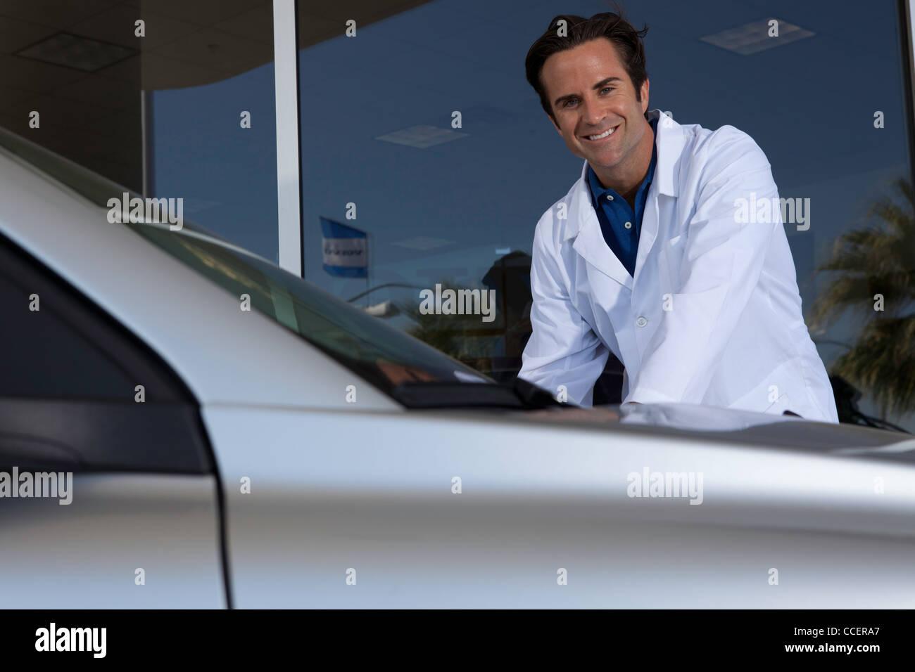 Fröhliche Autohändler stehen neben dem Auto Stockbild