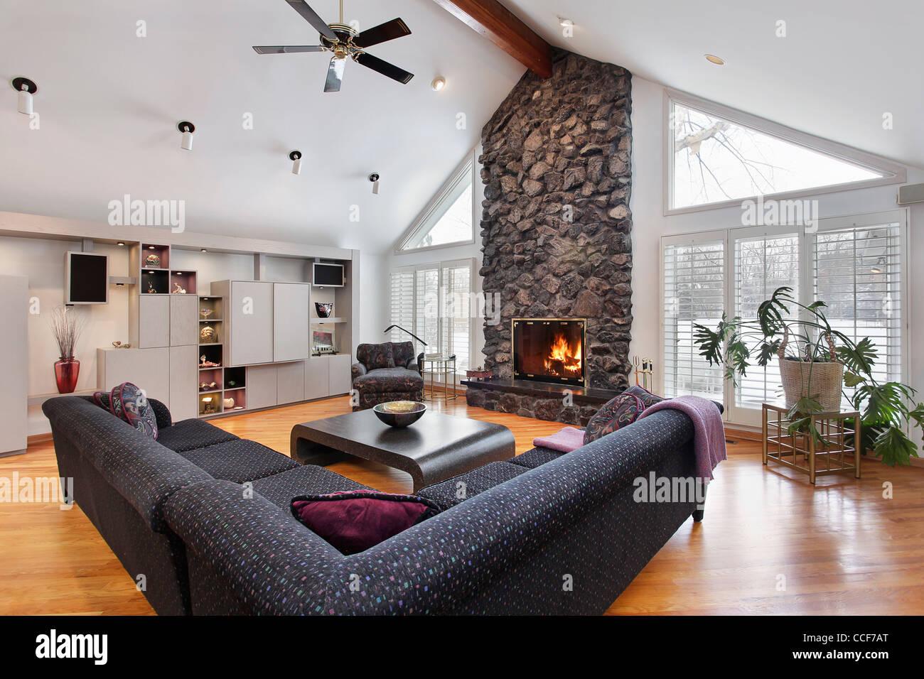familienzimmer mit zwei geschichte steinkamin und holzbalken - Steinkamin