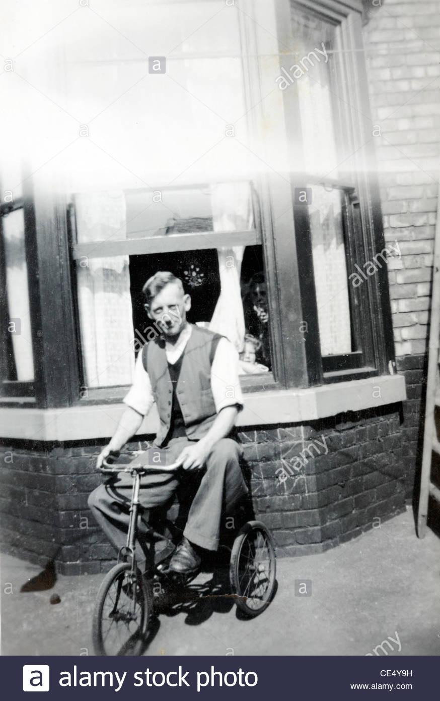 Erwachsene Person auf einem Kind Fahrrad posiert vor Haus England 1940er Jahre Stockbild