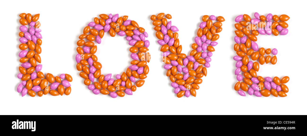 Wort Liebe bunte Muster hergestellt aus Dragee Bonbons isoliert auf weißem Hintergrund Stockbild