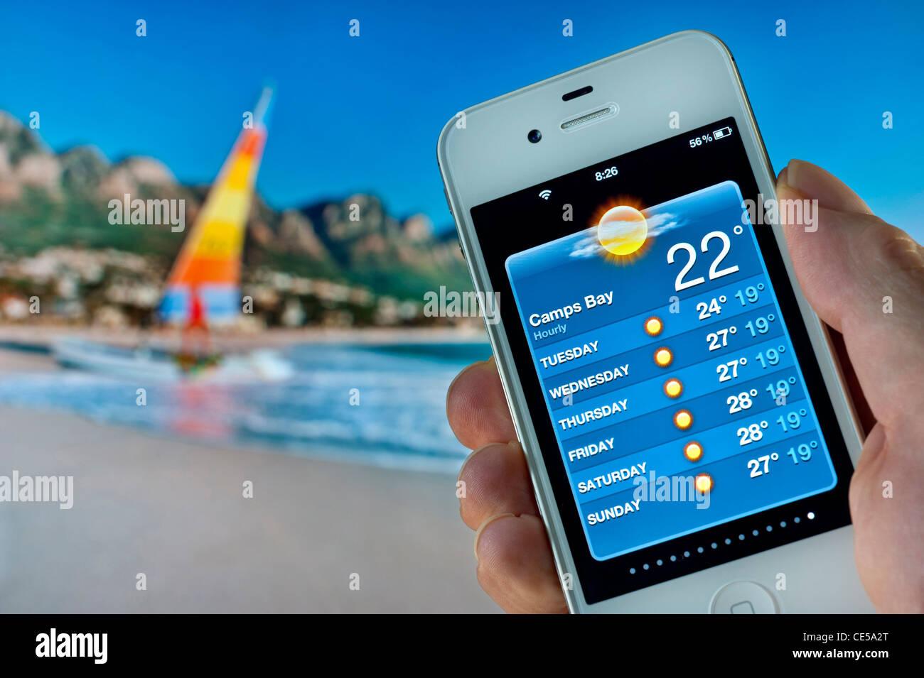 Hand, die weiße Apple iPhone anzeigen 22C Morgensonne auf Wettervorhersage Anwendung in Camps Bay Kapstadt Stockbild