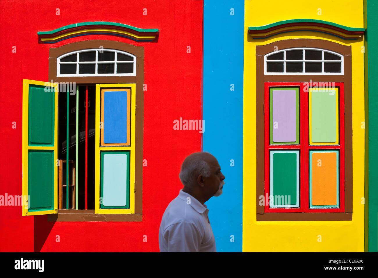 Mann zu Fuß vorbei an einem Colouful denkmalgeschützten Gebäude in Little India, Singapur Stockbild