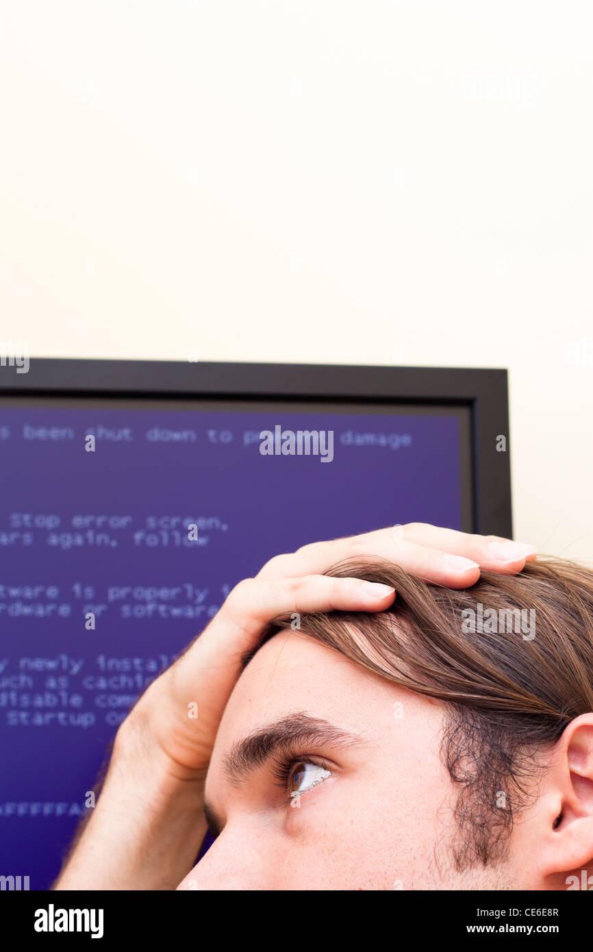 Unglücklicher Mensch Computer Fehlermeldung zu betrachten. Blue Screen of Death. Stockbild
