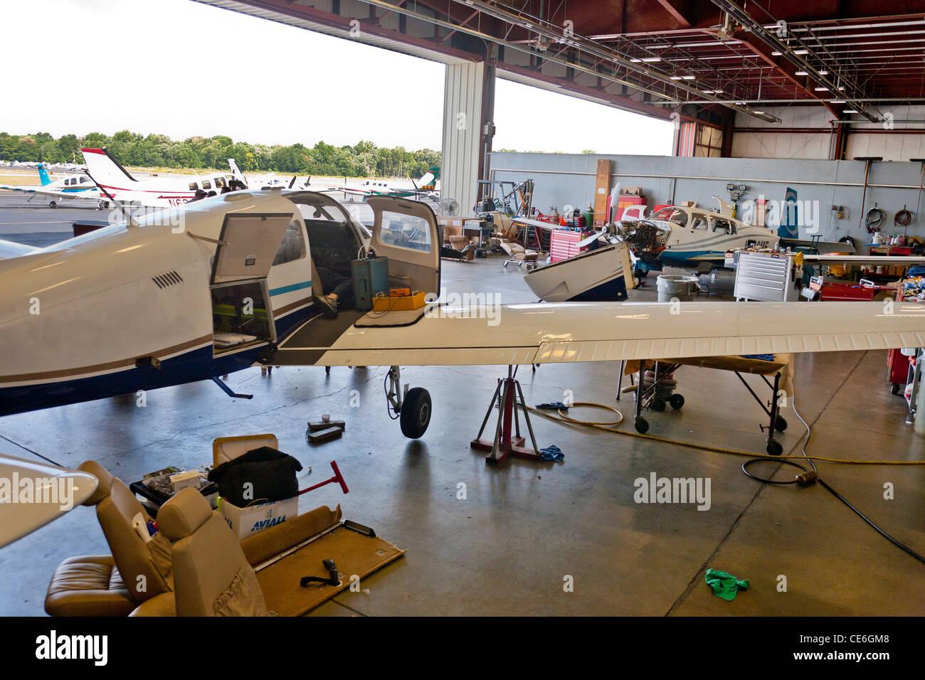 Eine Gruppe von Flugzeug sitzen im Inneren der Flugzeug-Kleiderbügel mit Flugzeugmotor Reparaturen durchgeführt Stockbild