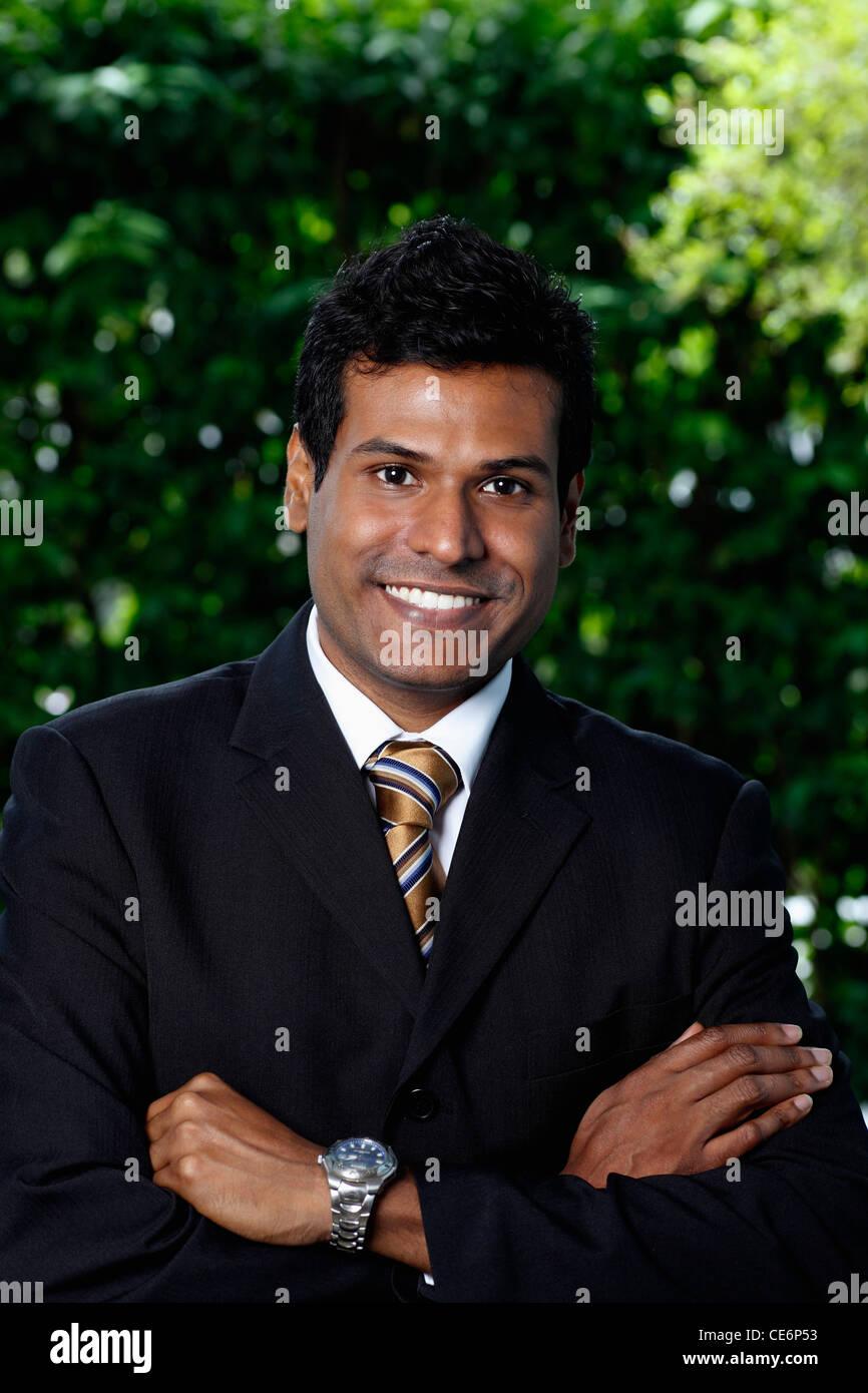 Porträt der indischen Mann Gelenkarme und lächelt in die Kamera Stockbild