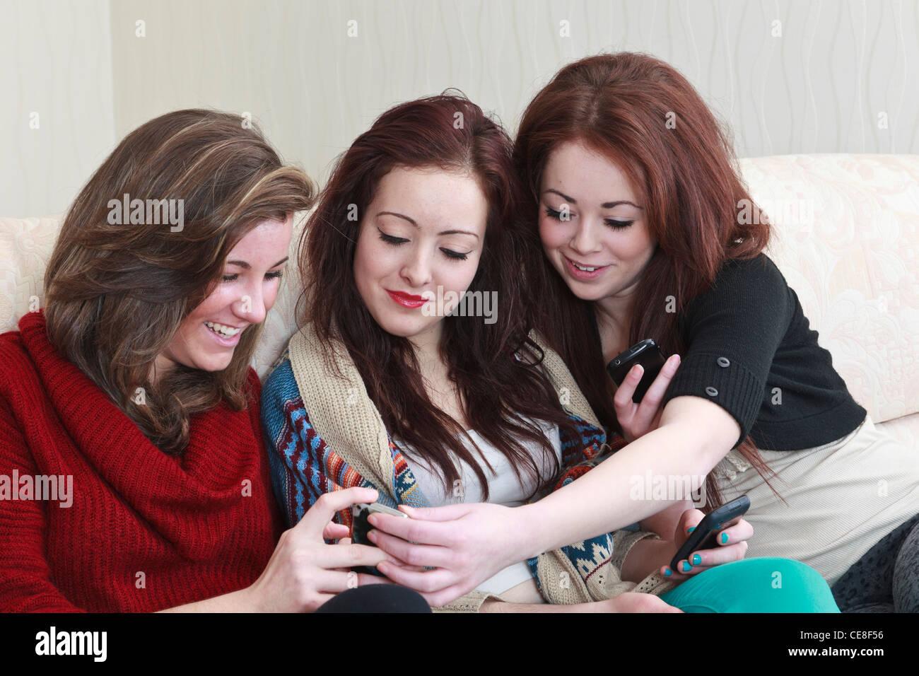 Drei generation z Jugendmädchen Freunde im Alter von 15 Jahren in einem Lachen von Fotos auf einem Mobiltelefon, Stockfoto
