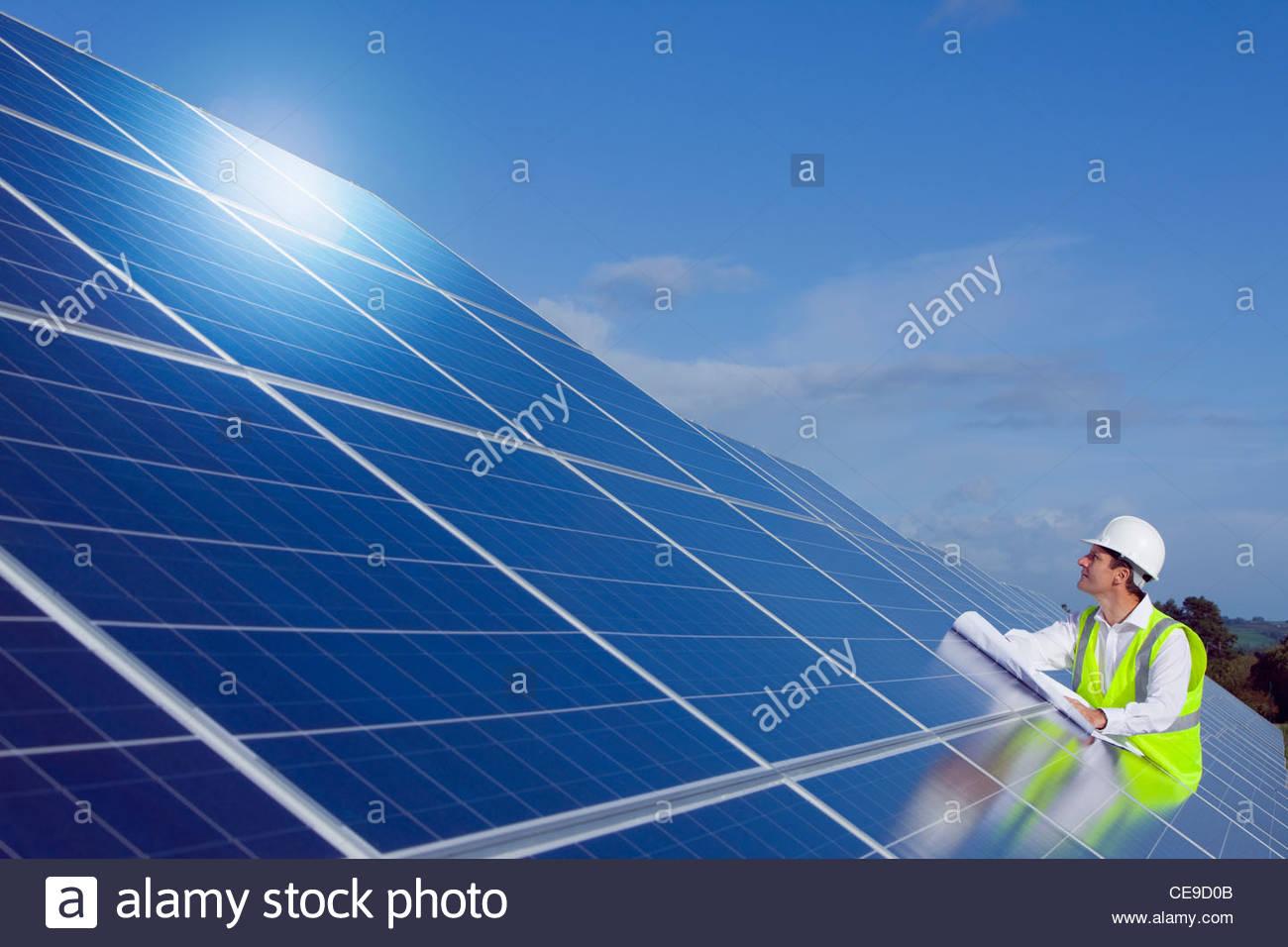 Ingenieur mit Blaupause Inspektion von Solarzellen Stockbild