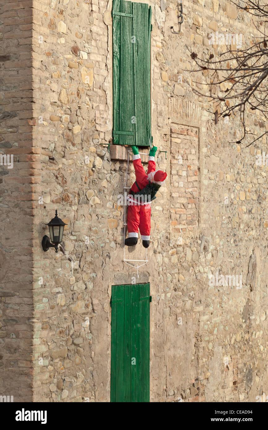 Aufblasbarer Weihnachtsmann Klettern auf einer Wand, Italien Stockbild