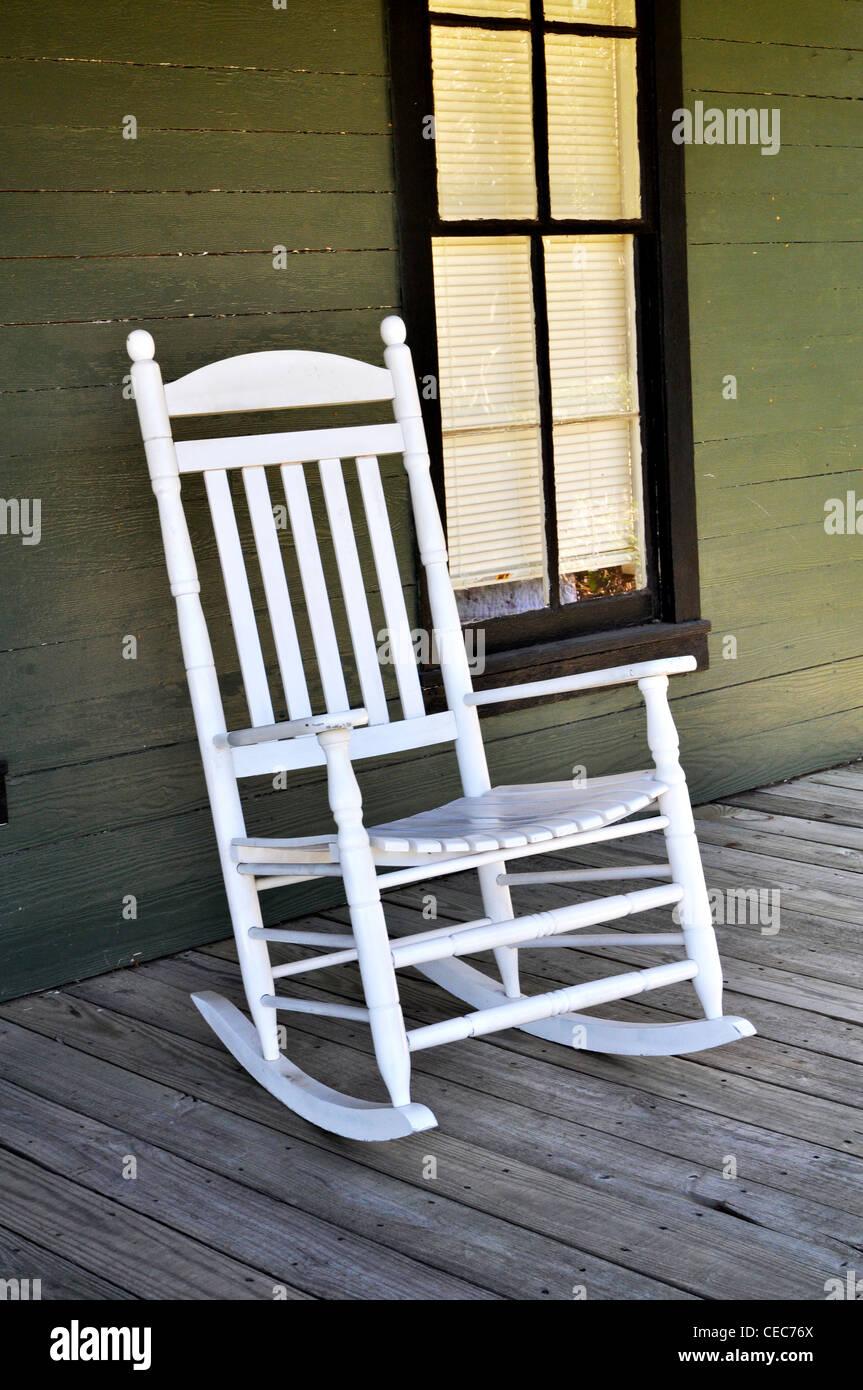 ein weißer holz schaukelstuhl sitzt auf der veranda stockfoto, bild