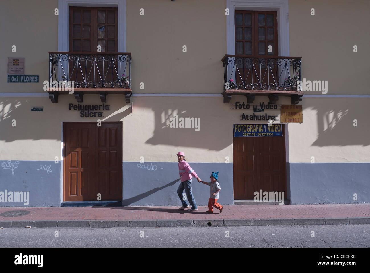 Eine ältere Schwester und hält die Hand ihres jüngeren Bruders, wie sie entlang einer Quito, Ecuador-Straße im späten Stockfoto