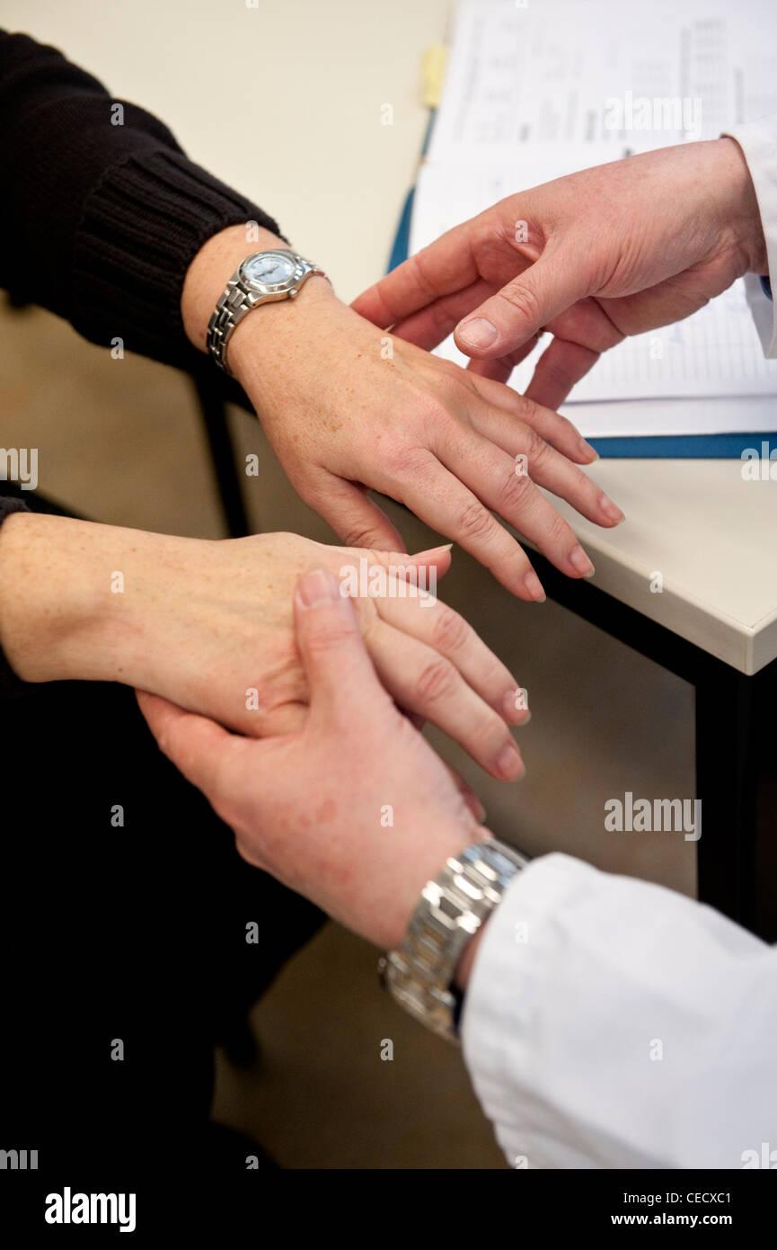 Ein Arzt am Universitätsklinikum Charité in Berlin Deutschland prüft eine weibliche Patienten Hände Stockbild