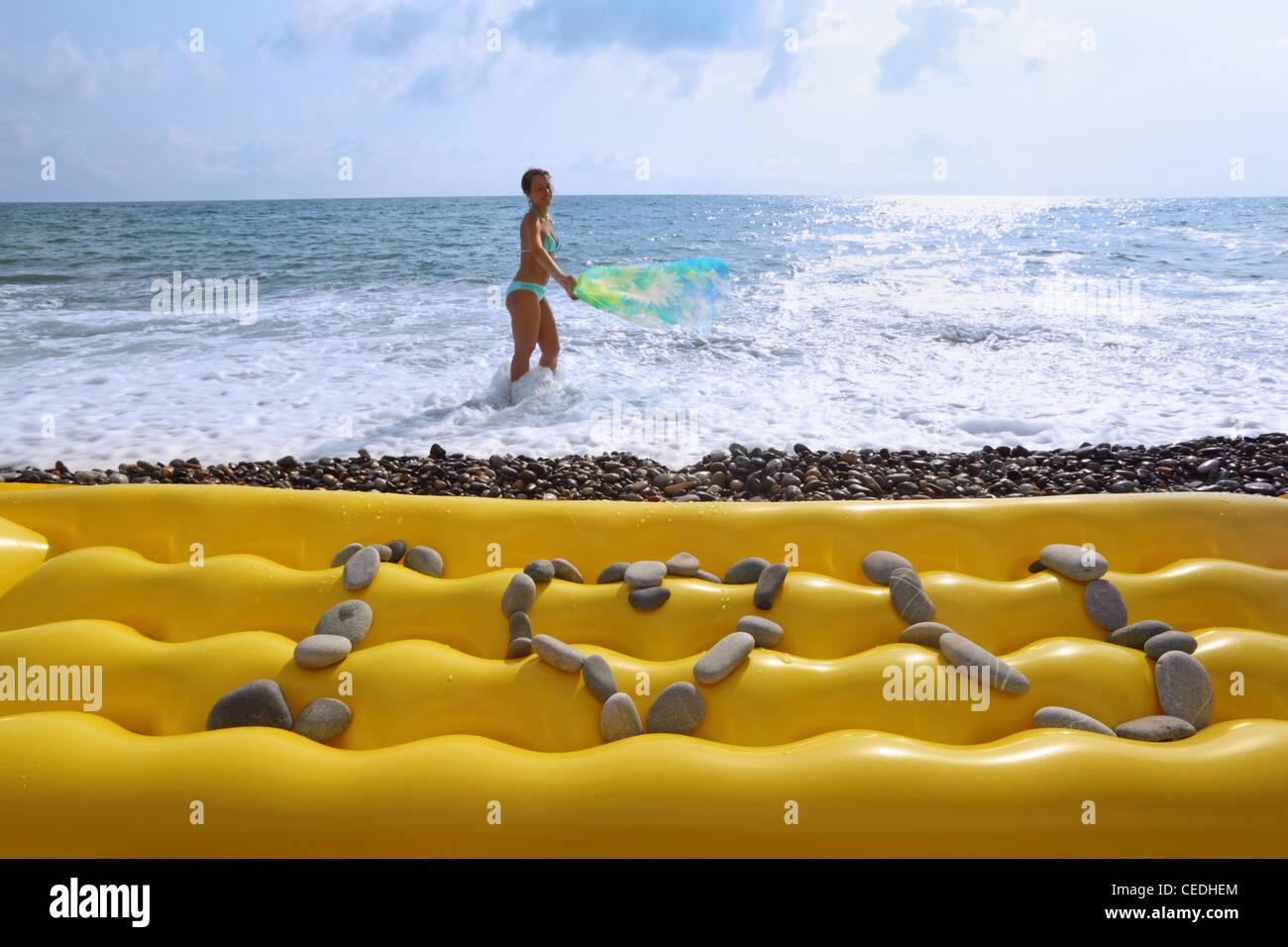 Aus Steinen ich liebe dich eine Inschrift auf gelbe Luft eng am Strand, schöne Frau mit Stoff am Ufer des Meeres Stockfoto