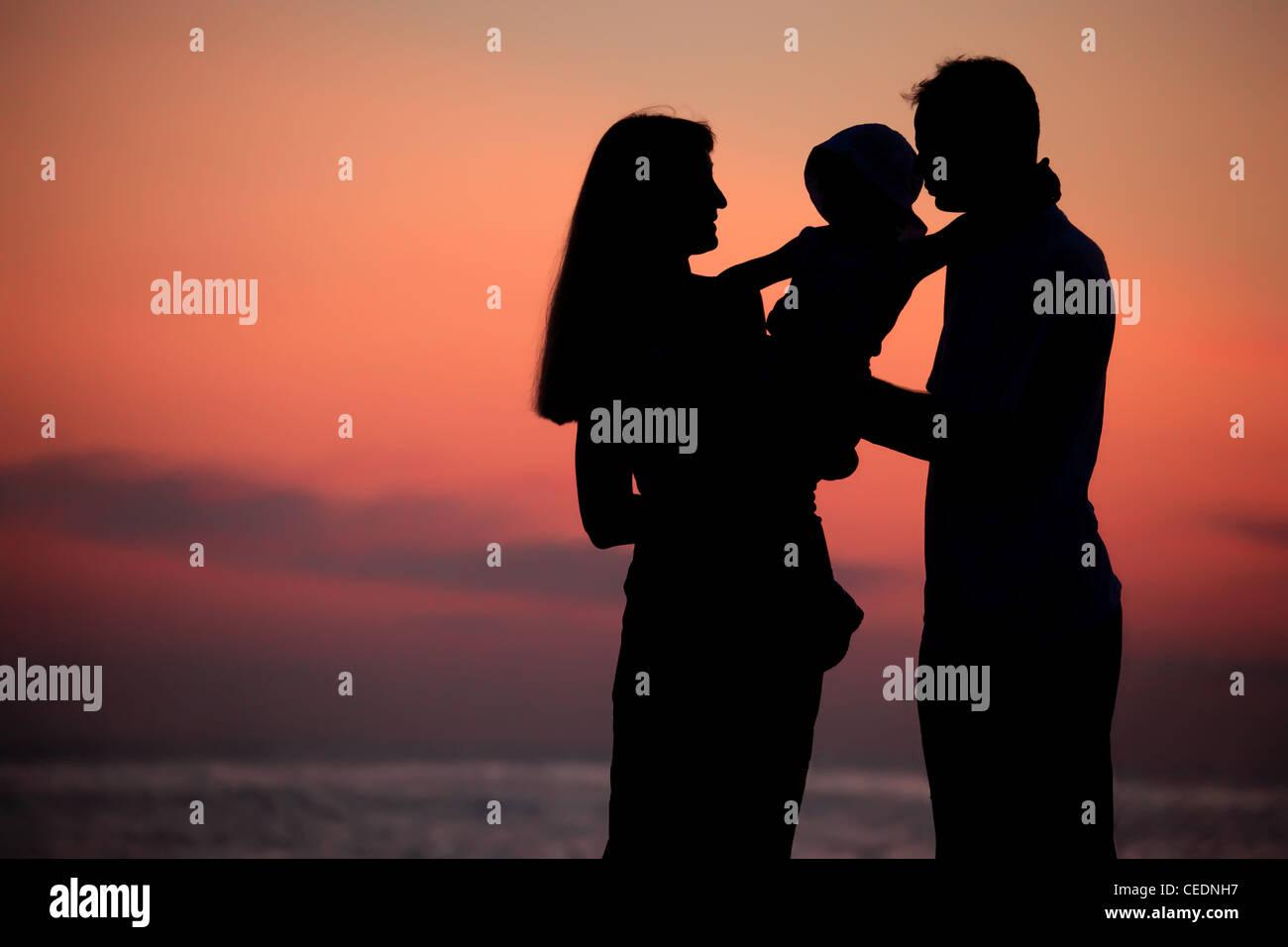 Silhouetten von Eltern mit Kind auf Händen gegen Meer sinken Stockbild