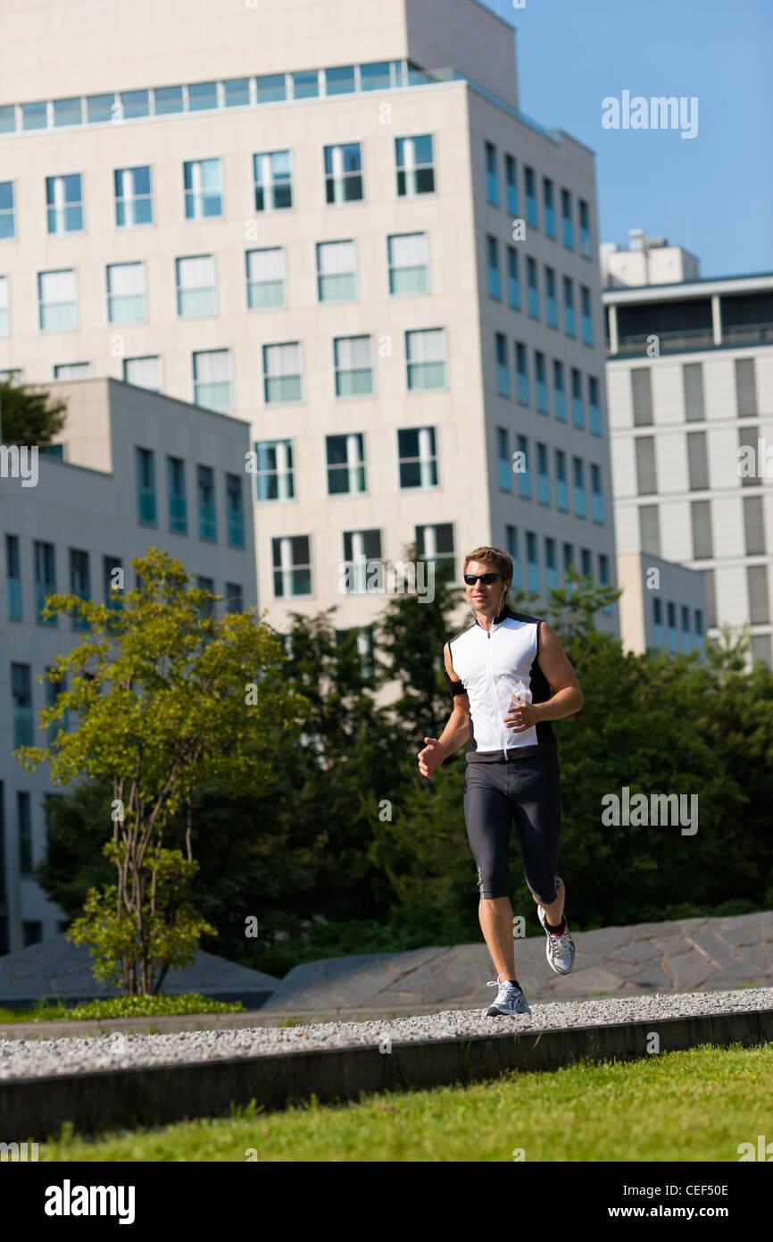 Urbane Sportarten - junger Mann Joggen für Fitness in der Stadt an einem schönen Sommertag Stockbild