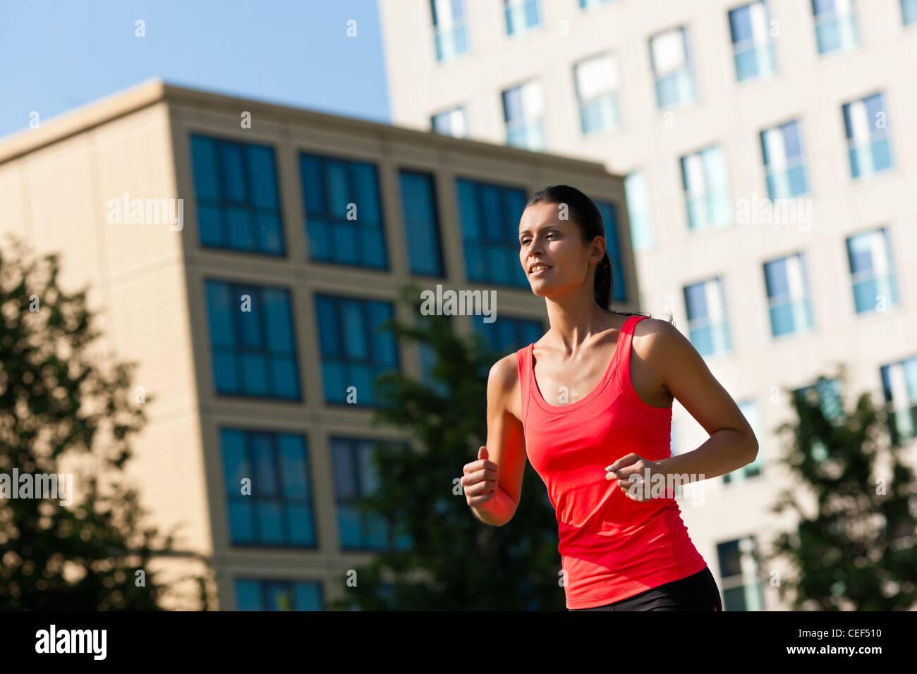 Urbane Sportarten - junge Frau Joggen für Fitness in der Stadt an einem schönen Sommertag Stockbild