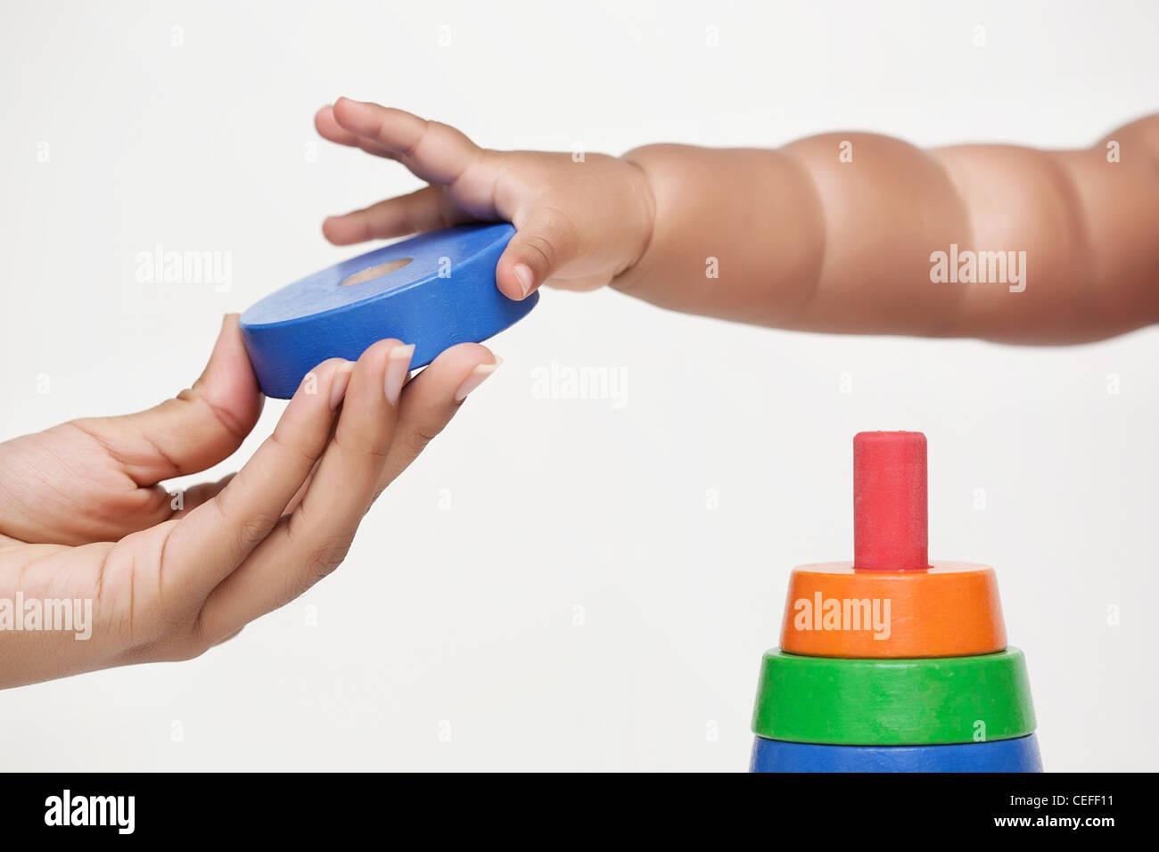 Erwachsenen Hand gibt einen Baustein und Baby lernt es halt Stockbild