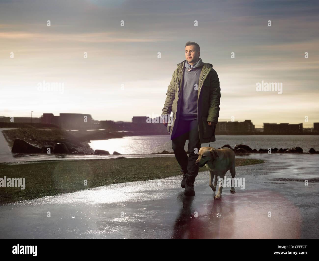 Mann zu Fuß Hund auf nasser Fahrbahn Stockbild