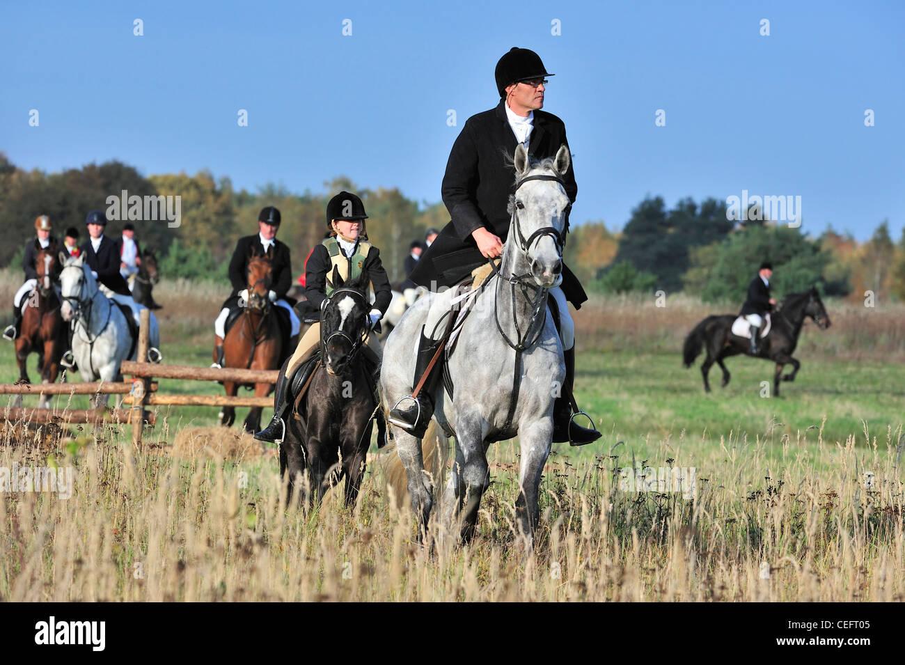 Jäger in schwarzen Mänteln zu Pferd folgen Sie künstliche Duft während des Ziehens / trail Jagd Stockbild