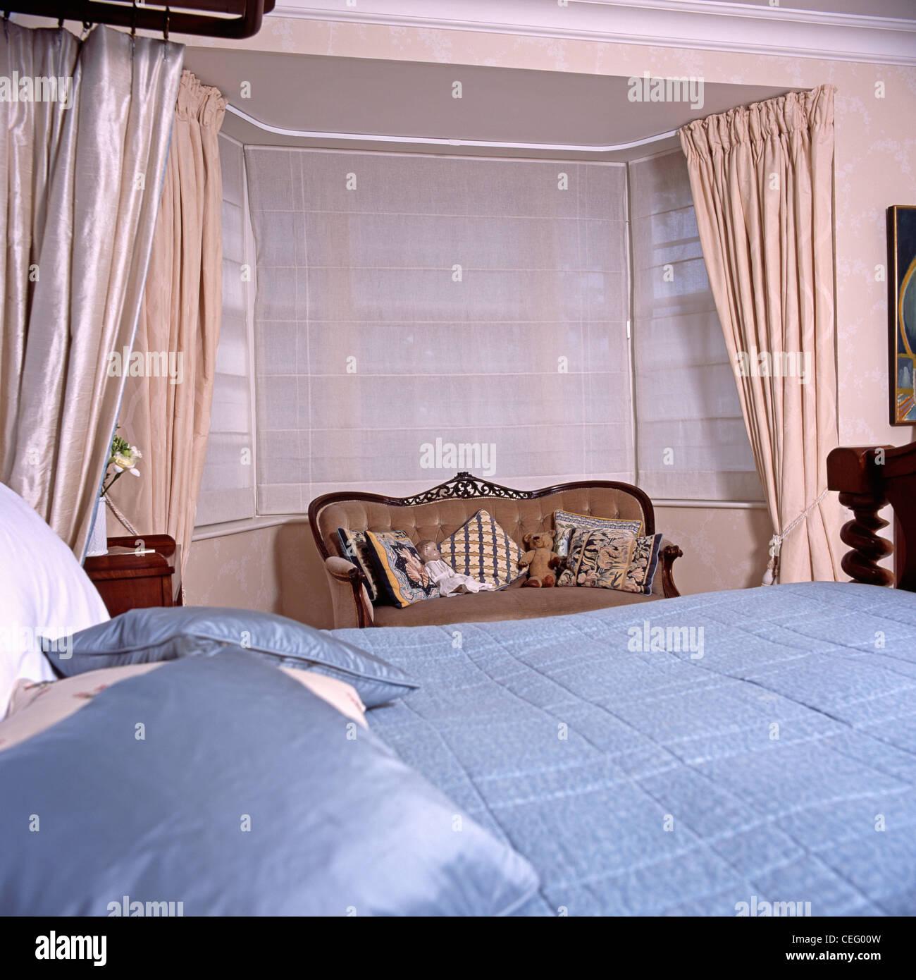 Blaue Seide Quilt In Traditionellen Schlafzimmer Mit Sofa Vor Erker Mit  Weißen Voile Vorhänge Und Creme Seidenvorhänge