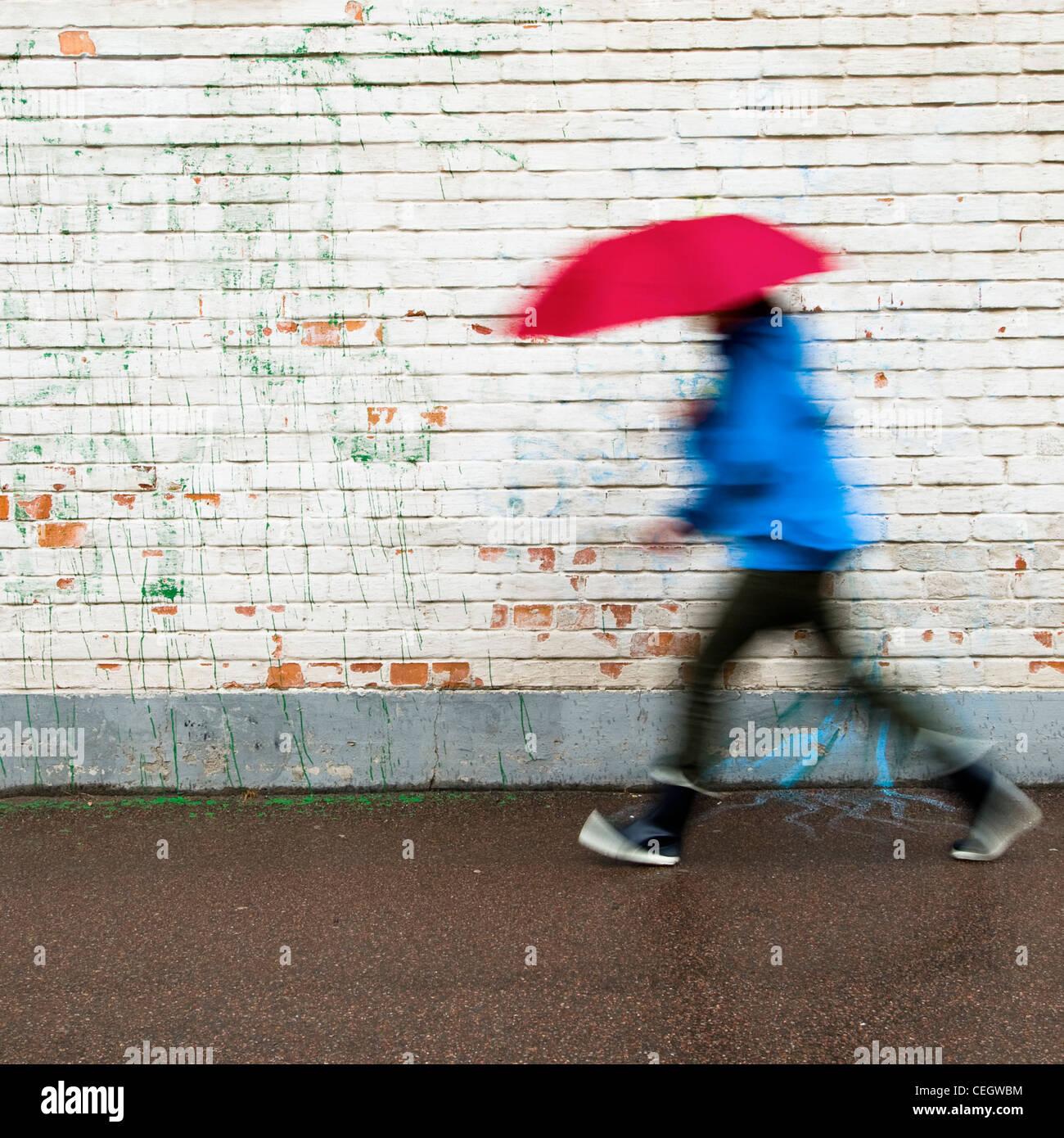 Person zu Fuß im Regen mit Regenschirm Stockbild