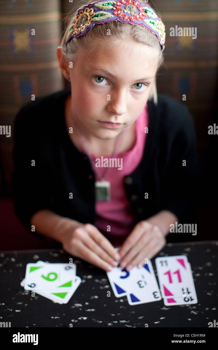 Mädchen-Spielkarten am Küchentisch Stockbild