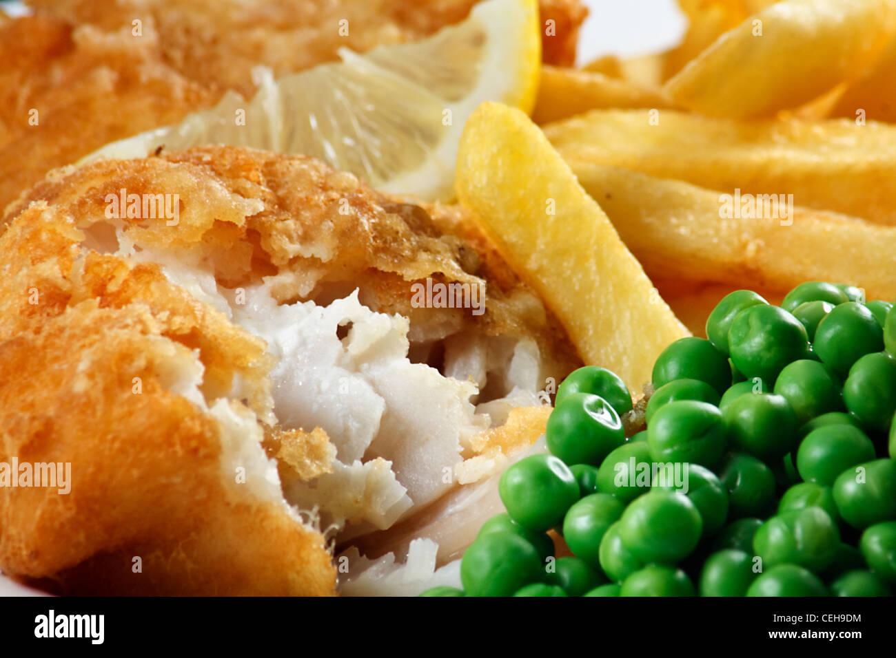 Nahaufnahme von Fish And Chips mit Erbsen und einer Scheibe Zitrone. Ein traditionelles Gericht der britischen Küste Stockbild