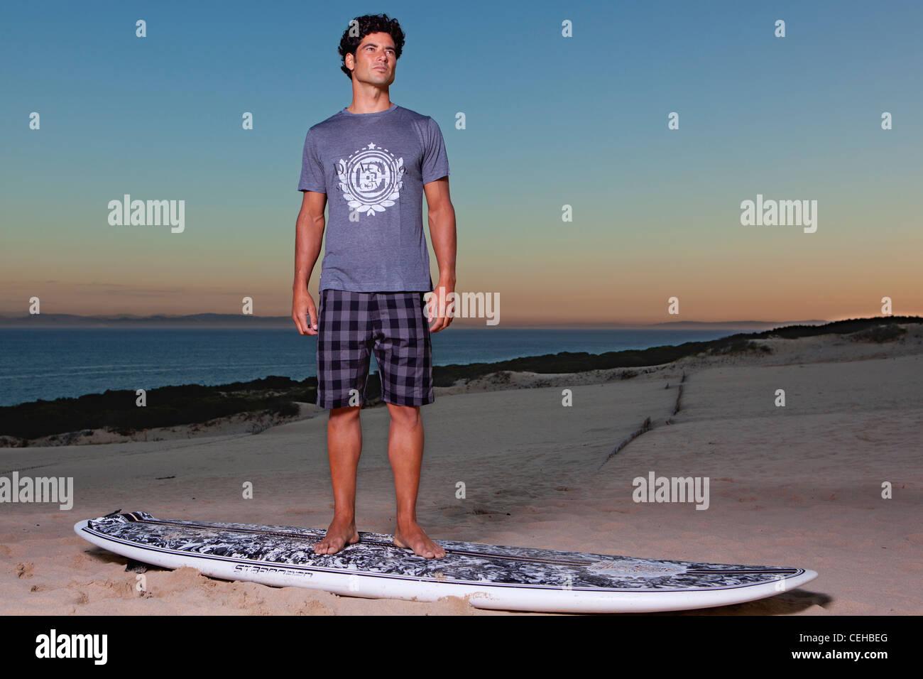 Junger Mann posiert am Strand über Ihr Surfbrett Stockbild