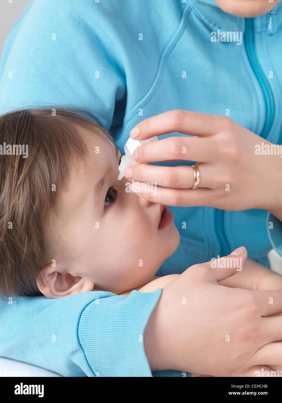Mutter gibt ihr zwei Jahre altes Kind Augentropfen Stockfoto, Bild ...
