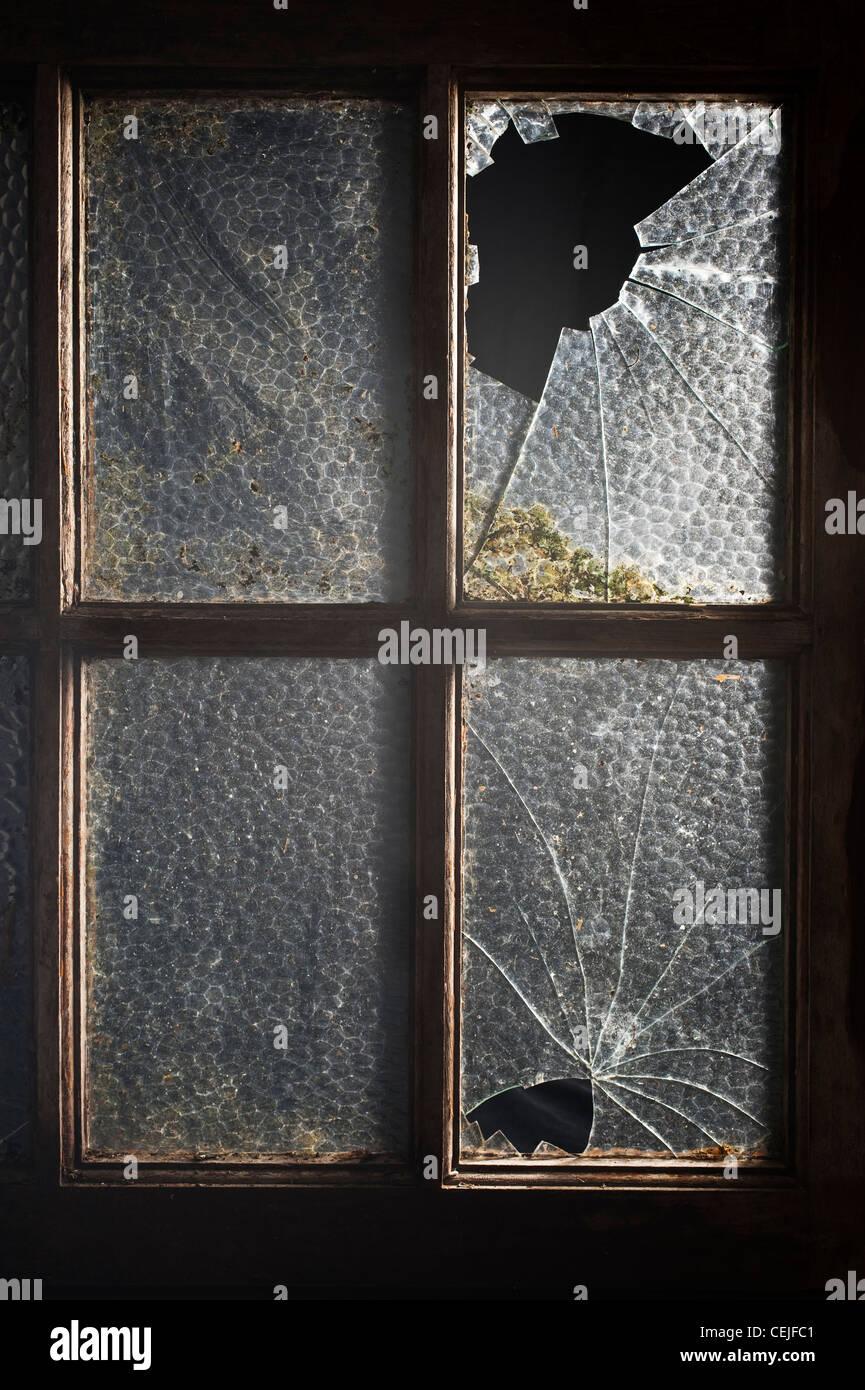 Ein altes Fenster mit zwei seiner Scheiben gebrochen Stockbild