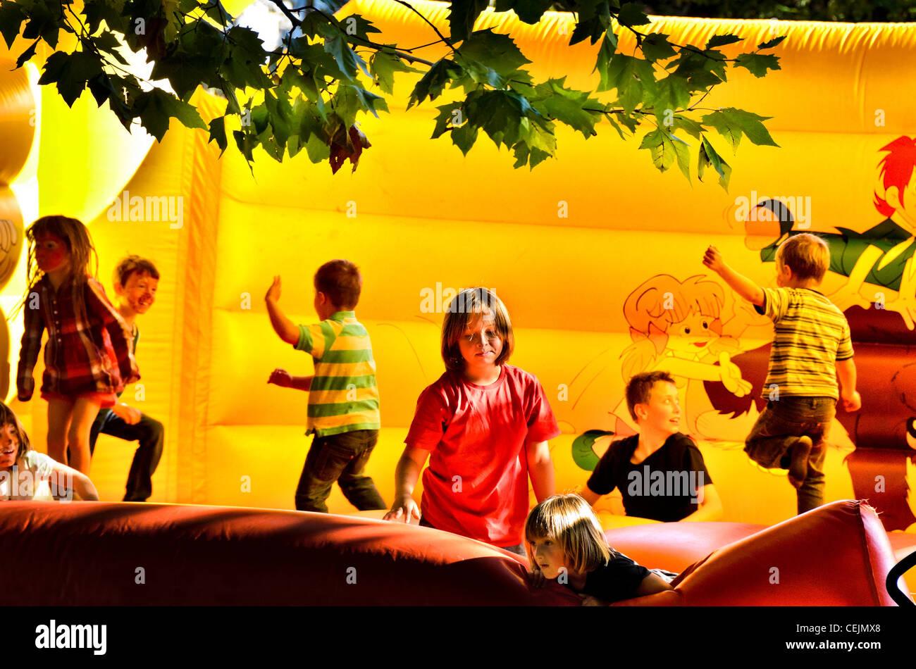 Kinder spielen auf einer Hüpfburg Stockbild