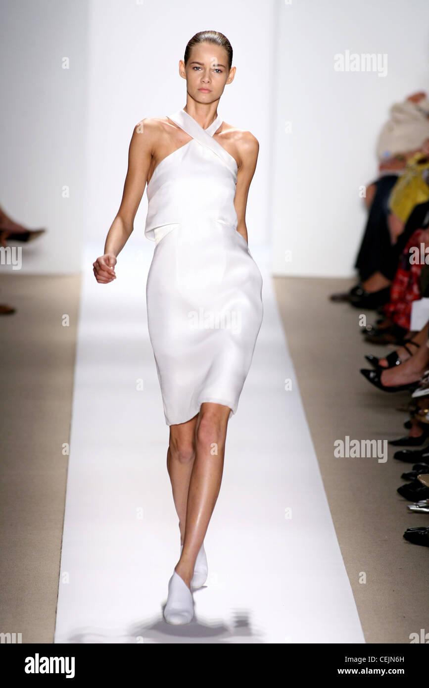 modell trägt ein weißes knie länge neckholder kleid mit