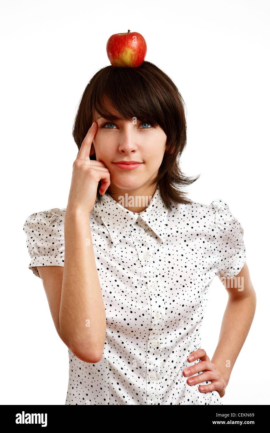 roter Apfel auf Mädchen Kopf - junge Frau schwer denken, auf weiß Stockbild