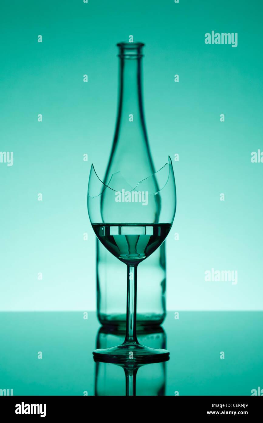 zerbrochenes Glas - kurz gefasst und eine Flasche - unscharf Stockbild