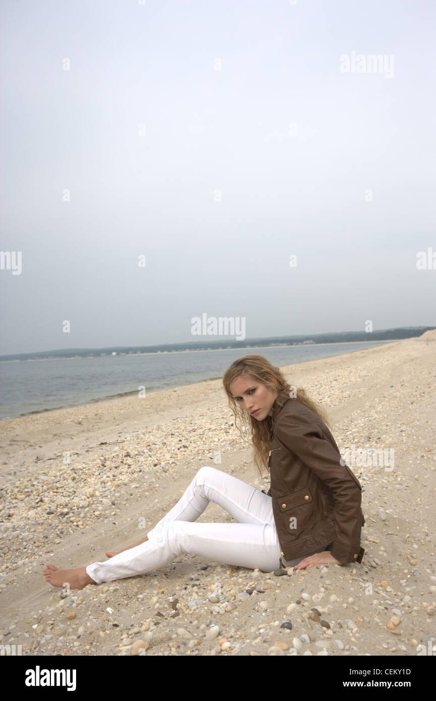 ce246b7ca62a Weibchen trägt eine braune Jacke und Weiße Röhrenjeans sitzen an einem  Strand Frowein Stockbild