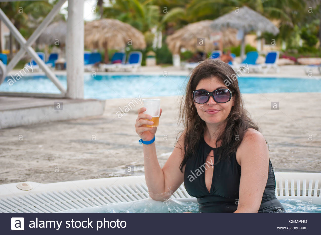 latin girl mit einem bier in einem jacuzzi genie en einen urlaub in ein tropisches reiseziel. Black Bedroom Furniture Sets. Home Design Ideas