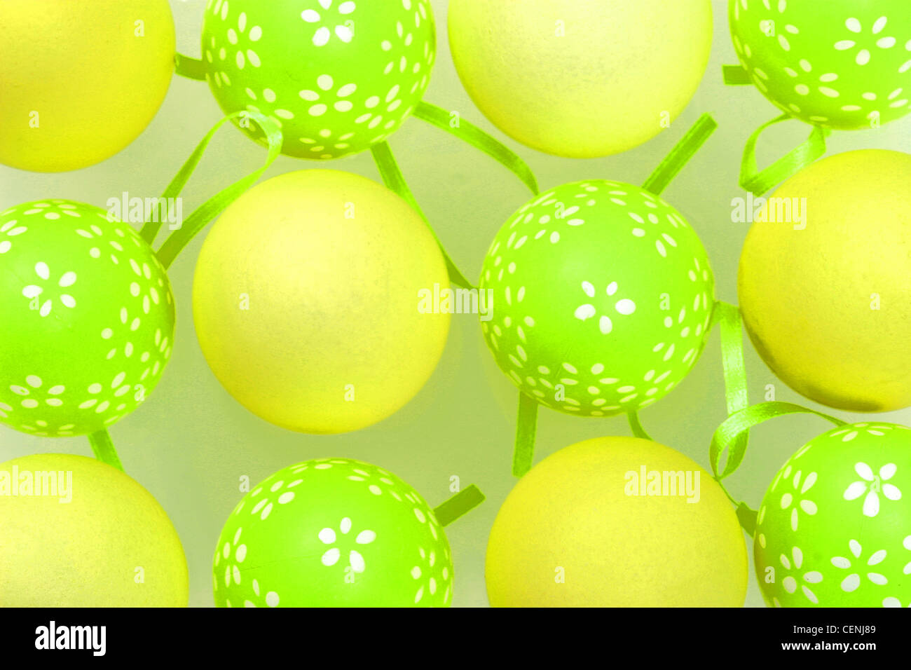 Eiern malte grünen Eiern weißen Blumenmuster, arrangiert abwechselnd blass gelben Eiern grüne Bänder Stockbild