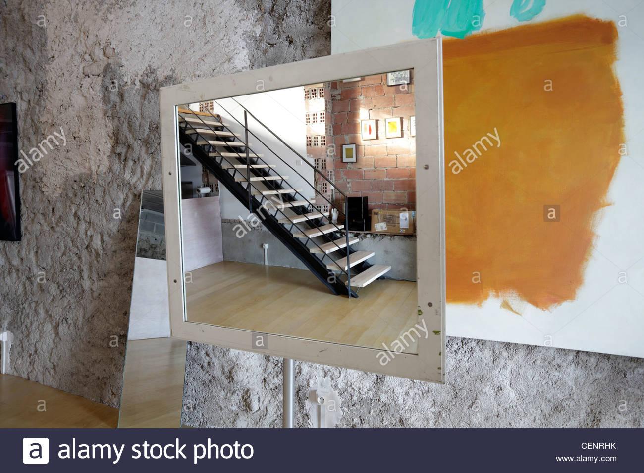 Spiegel in einem Raum mit Kunstwerken an den Wänden platziert. Stockbild