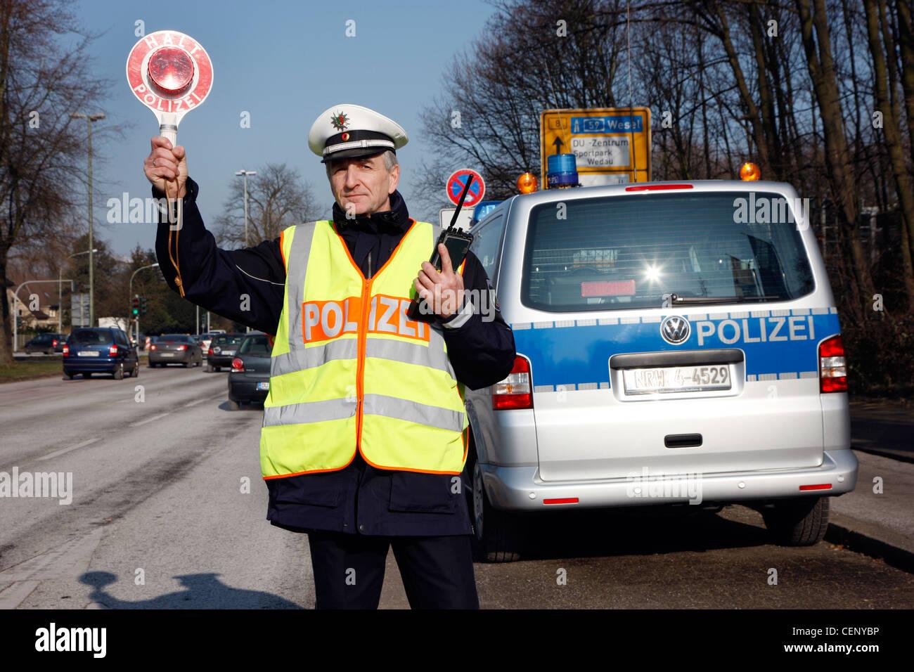 Polizeikontrolle, Verkehr Drehzahlregelung, Polizist stoppt Autos auf einer Straße. Stockbild