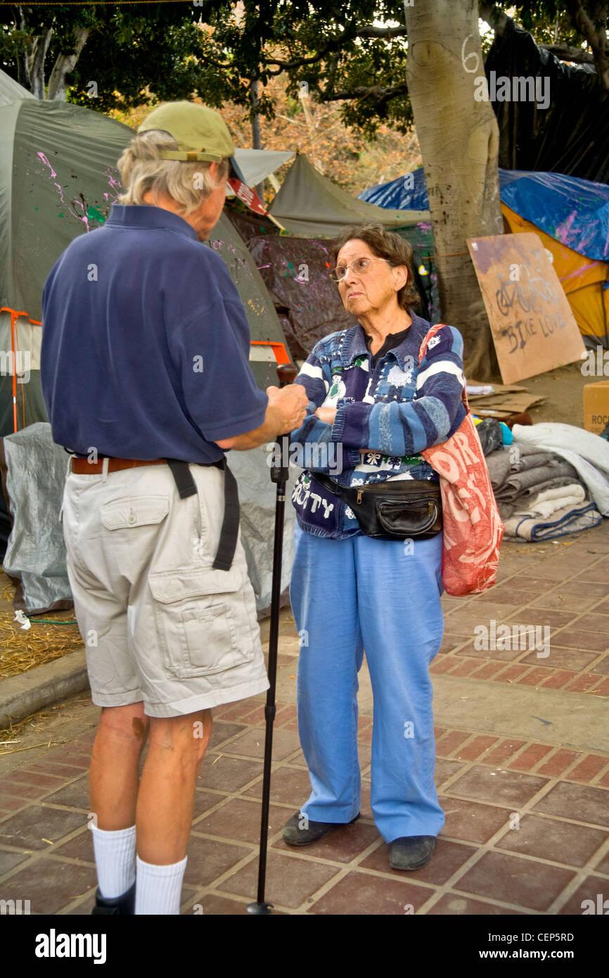 Eine skeptische ältere Frau konfrontiert ein Kritiker der Occupy Wall Street Besetzung in Los Angeles City Stockbild