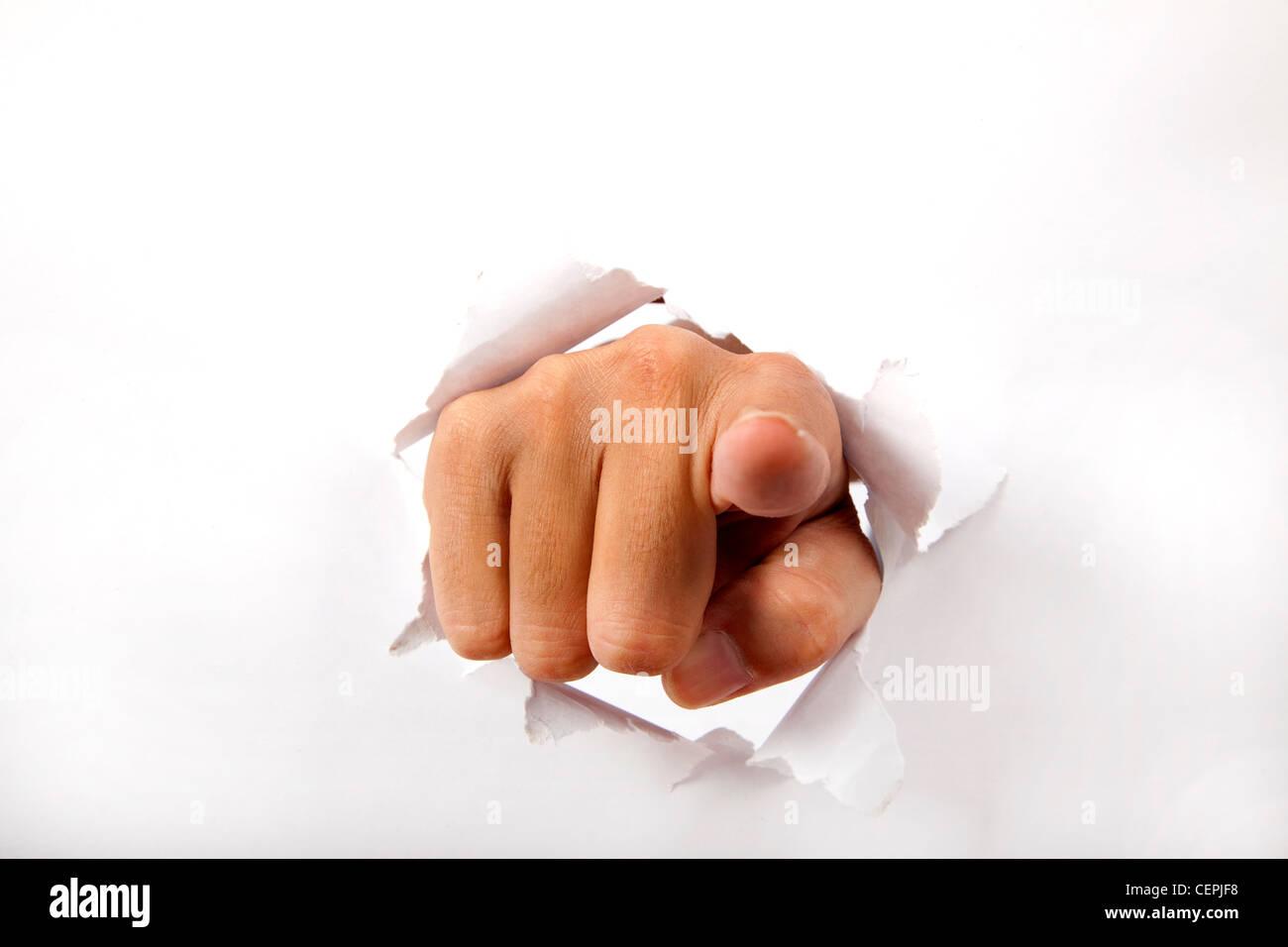 Hand zu brechen durch das Weißbuch mit Fingerzeig auf die Sie Stockbild