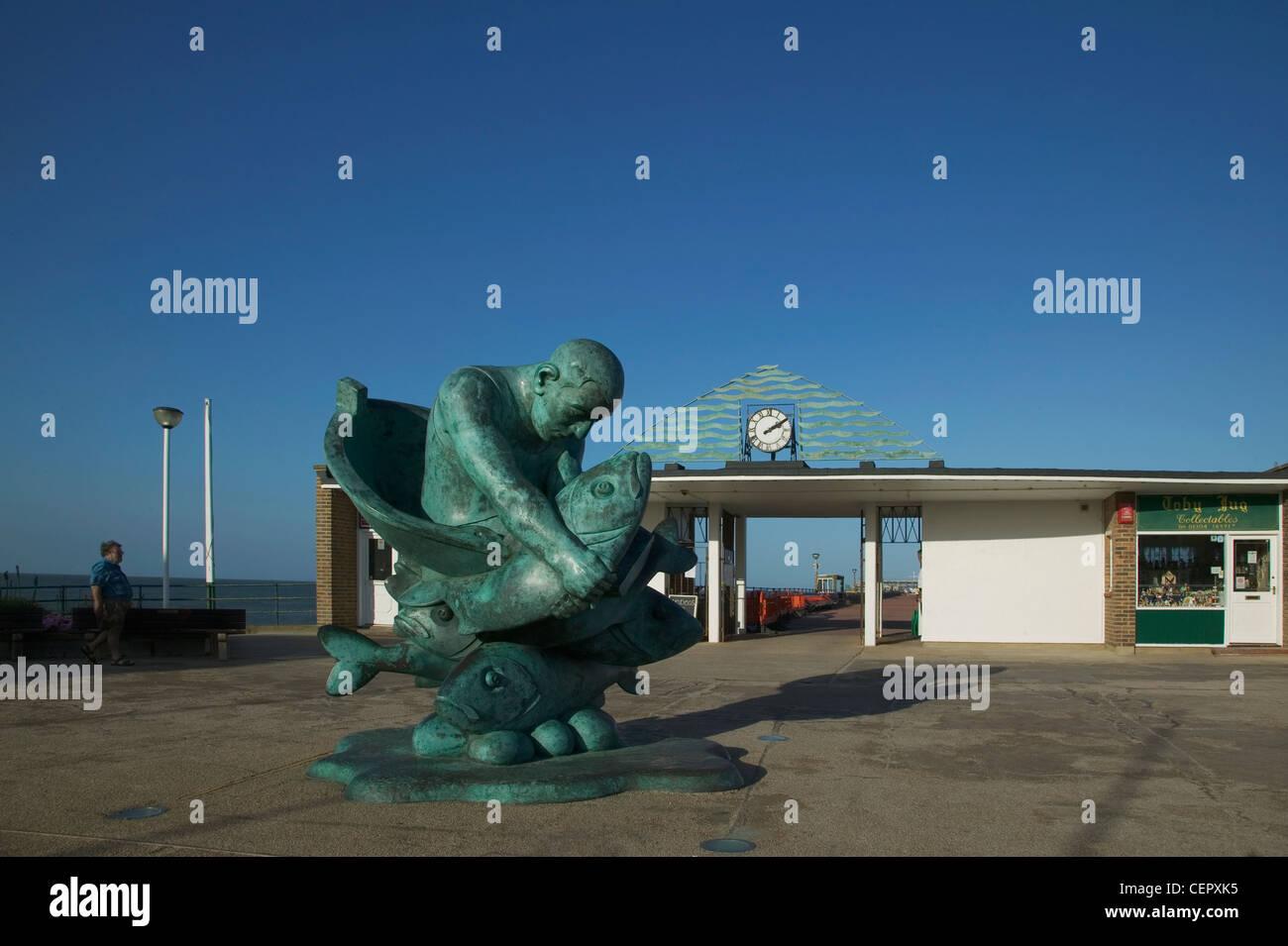 """Die Statue von Alan Yates hält ein riesiges Seebarsch mit dem Titel """"Embracing am Meer"""" von Jon Buck Stockbild"""