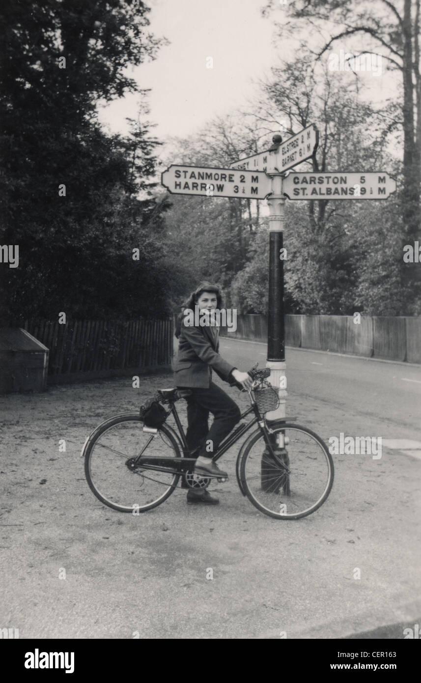 Archivfoto: Frau auf einem Fahrrad in der Nähe von Wegweiser (c1945) Stockfoto