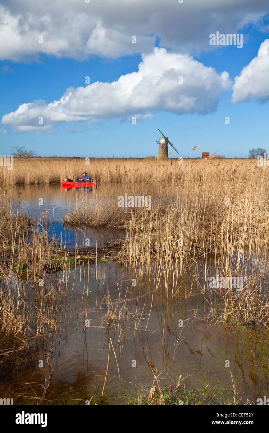 Kanufahrer auf dem Fluß Thurne mit der verfallenen Heigham Holmes Mühle am Eelfleet Deich in der Ferne Stockbild