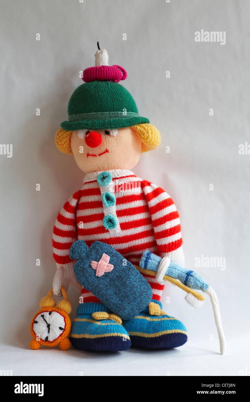 gestrickte Puppe - wee Willie Winkie mit Kerze auf Kopf, Wärmflasche, Wecker, Zahnbürste, Zahnpasta mit Paste zu Stockfoto