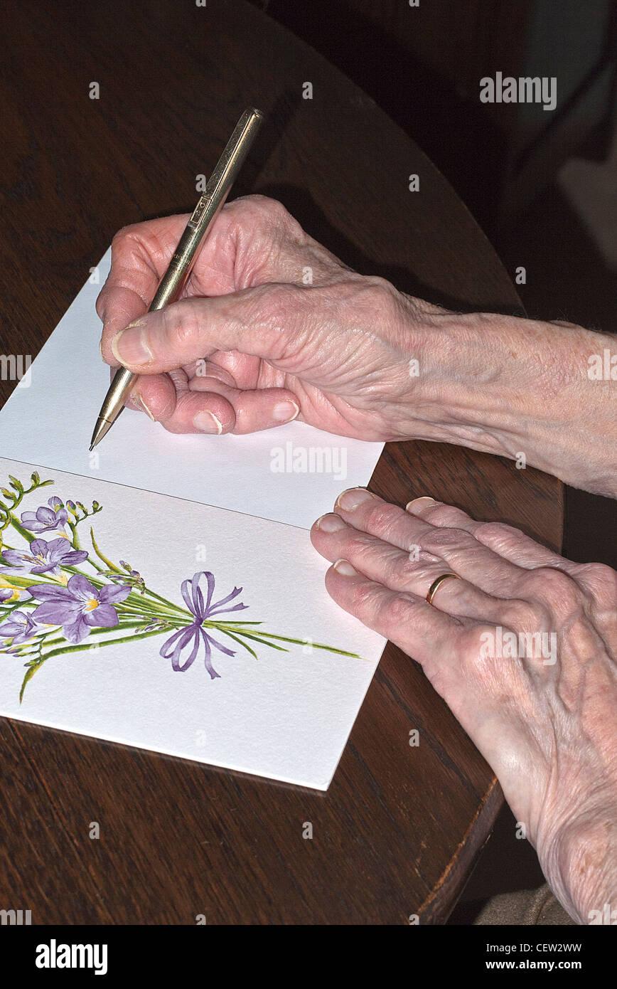 Hände Einer Dame schreiben Sie eine Grußkarte, UK. Stockbild