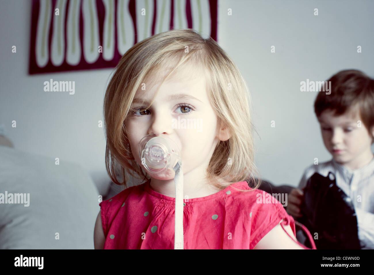 Kleine Mädchen saugen Schnuller Stockbild
