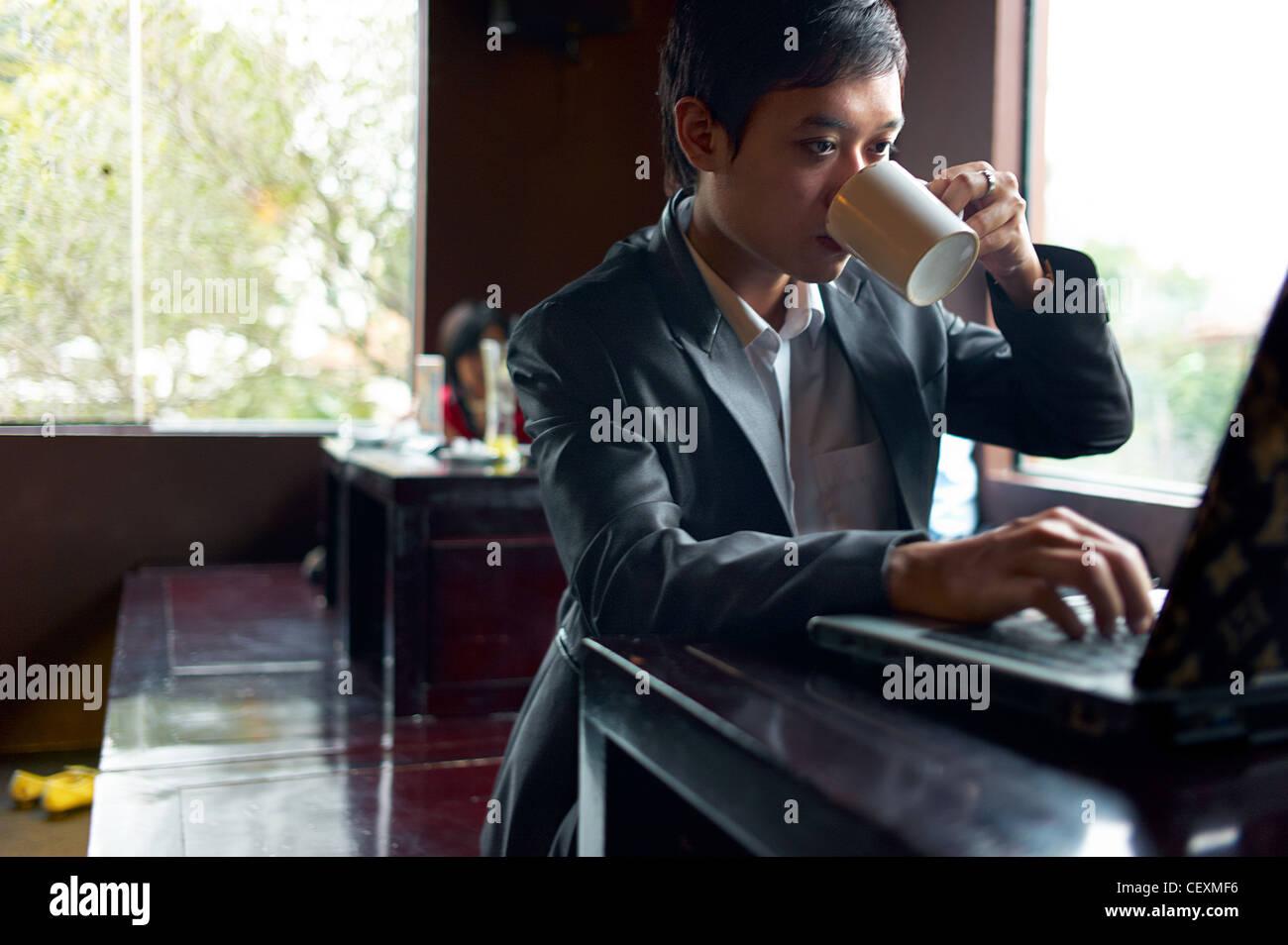 Ein junger Geschäftsmann trinkt Kaffee während der Arbeit an seinem Laptop in einem Café in Hanoi, Stockbild